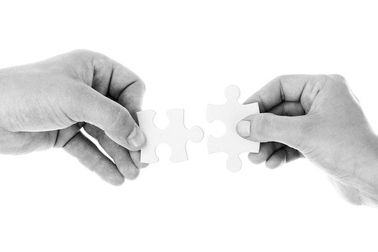 Two hands joining two pieces of a puzzle, symbolizing the conjunction of digital marketing and customer service to enhance business growth.