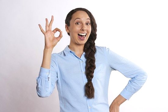 A girl with a smile on her face, showing OK with her fingers.