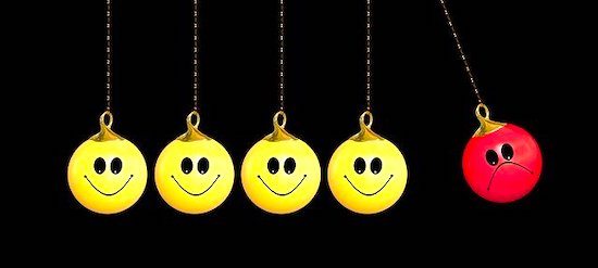 Alt: Newton's cradle with four yellow smiley faces and one red sad face instead of metal balls.
