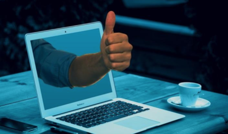 A hand making a thumbs-up gesture through a laptop screen.